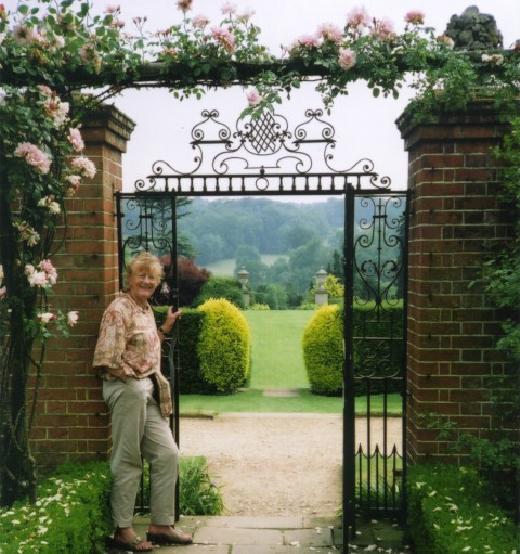 Dr. Barbara Sommerville at the pretty wrought Iron gate of the Rose Garden at Polsden Lacy, Surrey. Beyond is the stunning North Chalk Down scenery.